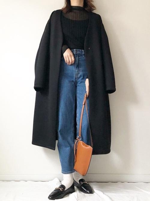 黒のシアーリブトップスに黒のノーカラーコートを羽織り、ストレートデニムと黒のローファーを合わせキャメル色のショルダーバッグを持ったコーデ