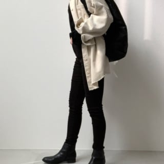 カットソーにスキニーデニムとアンクルブーツを合わせた黒のワントーンに白のニットカーディガンを羽織り、黒のリュックを肩掛けしたコーデ