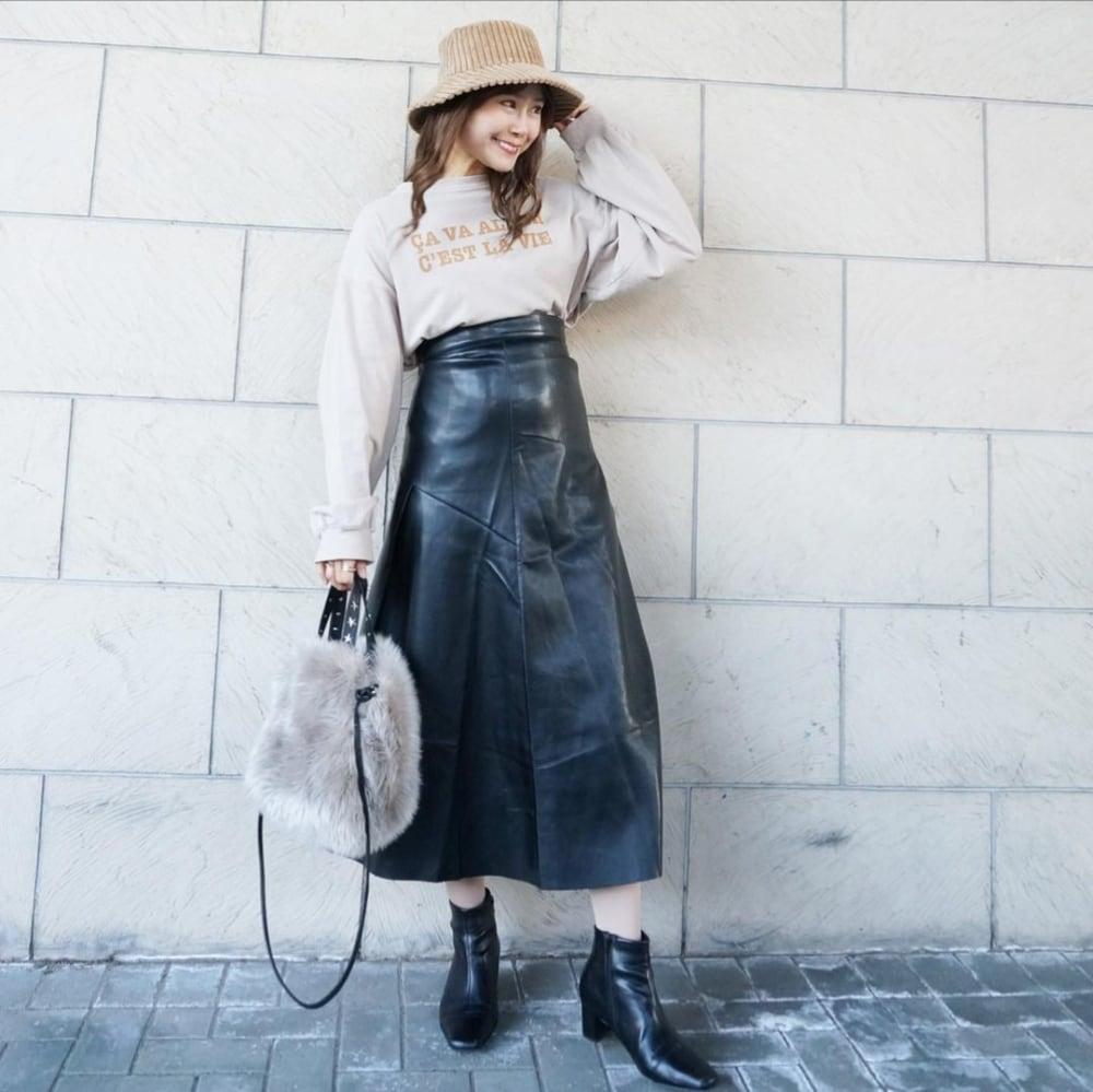 長袖ロゴスウェットに黒のレザーのフレアスカートとレザーブーツを合わせ、コーデュロイのバケットハットとグレーのファーバッグを用いたコーデ