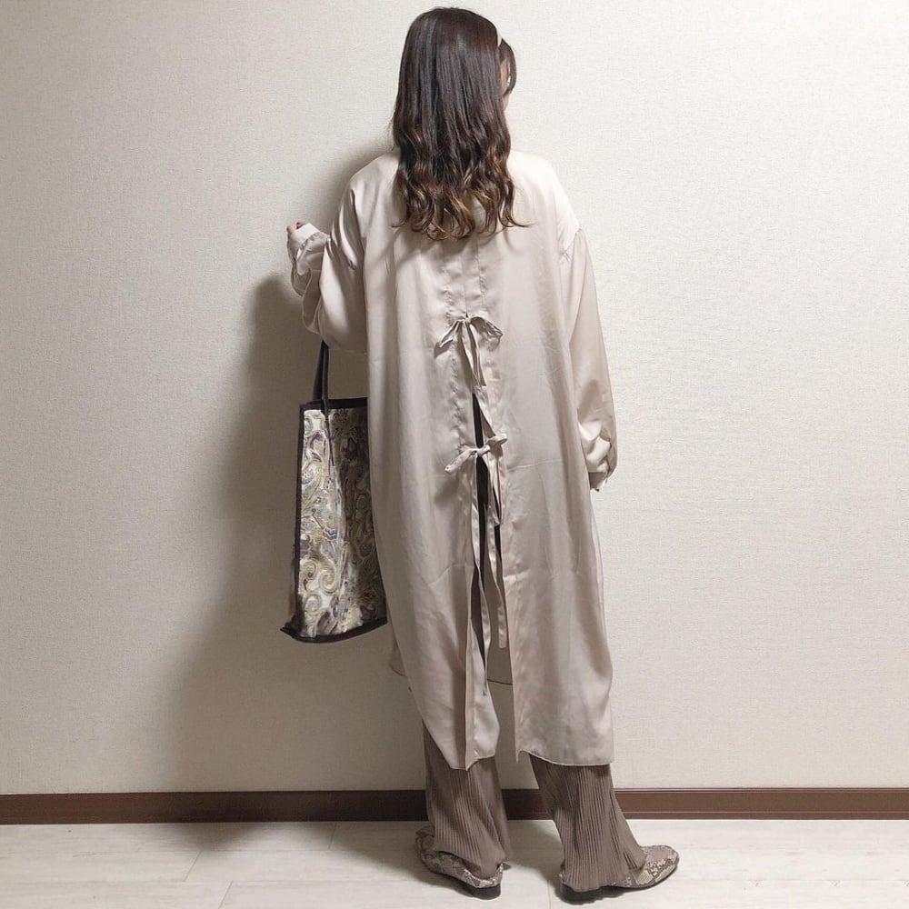 オフベージュのロング丈のバックリボンシャツワンピにブラウンのプリーツパンツを合わせ、トートバッグを持ったコーデ