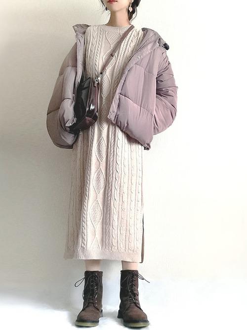 ベージュのケーブル編みニットワンピースにブラウンのダウンジャケットを羽織り、ブラウンのショルダーバッグとラバーソールレースアップブーツを合わせたコーデ