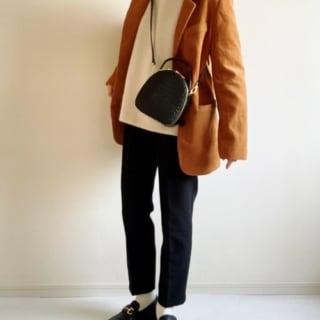 白のタートルニットにキャメル色のテーラードジャケットを羽織り、黒のテーパードパンツとローファーを合わせ、黒のショルダーバッグをななめ掛けしたコーデ