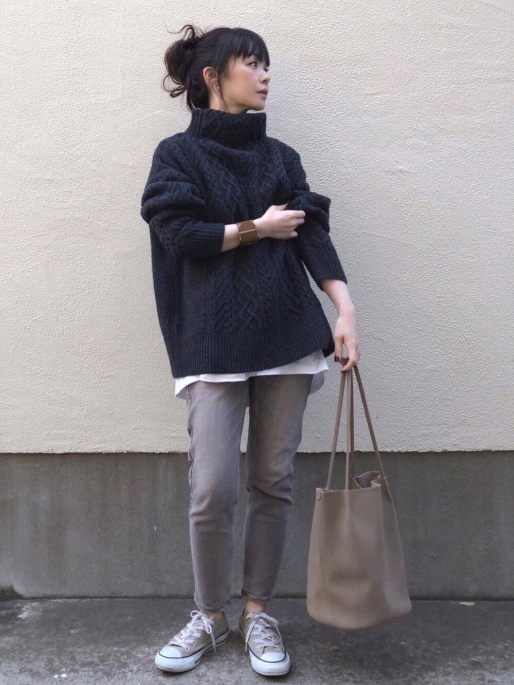 グレーのデニムパンツに黒ニットと白カットソーの重ね着コーデ