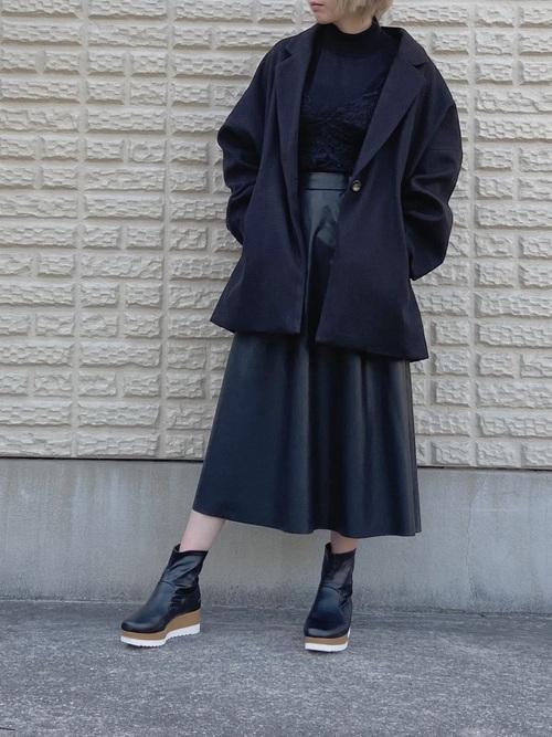 ニットにテーラードジャケットを羽織りレザーフレアスカートを合わせ、厚底ブーツを履いた黒のワントーンコーデ