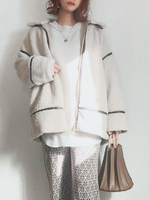 白のクルーネックニットに白のパイピングボアジャットを羽織り、柄パンツとプリーツバッグを合わせたコーデ