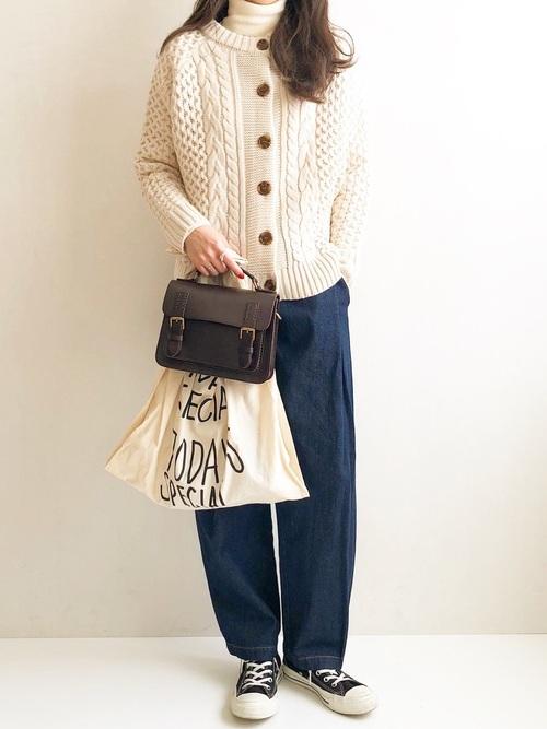 白のタートルネックニットに白のケーブル編みニットカーディガンを羽織り、青のパンツと黒のバッグと白のトートバッグをコーディネート