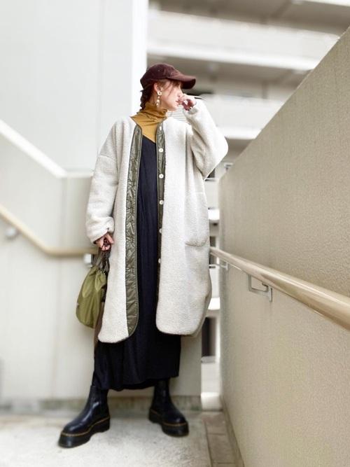 ブラウンのキャップをかぶり、ベージュのタートルに黒のキャミワンピをレイヤードし、白のボアロングコートを羽織り、黒のサイドゴアブーツとカーキ色こバッグをコーディネート