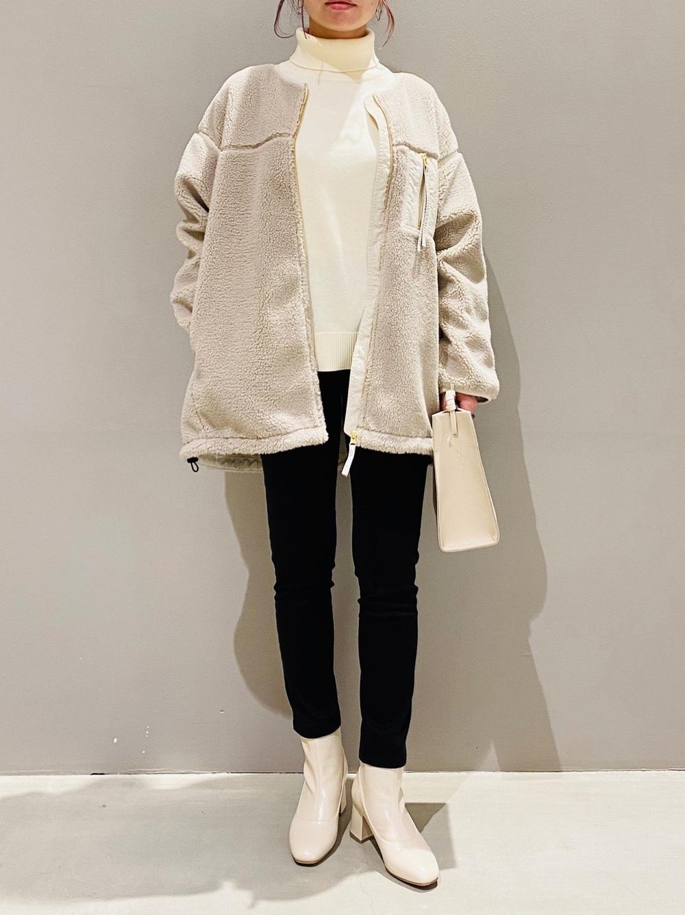 白タートルネックニットと白ボアジャケットに黒スキニーと白ブーツのコーデ