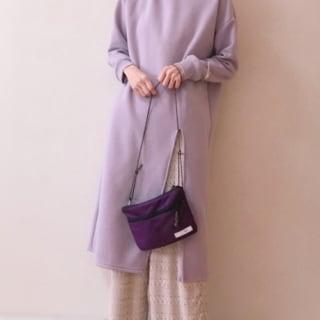 くすみパープルのスリット入りロングパーカーにベージュの透かし編みパンツと白のレースシューズ、濃い紫のショルダーバッグを合わせたコーデ