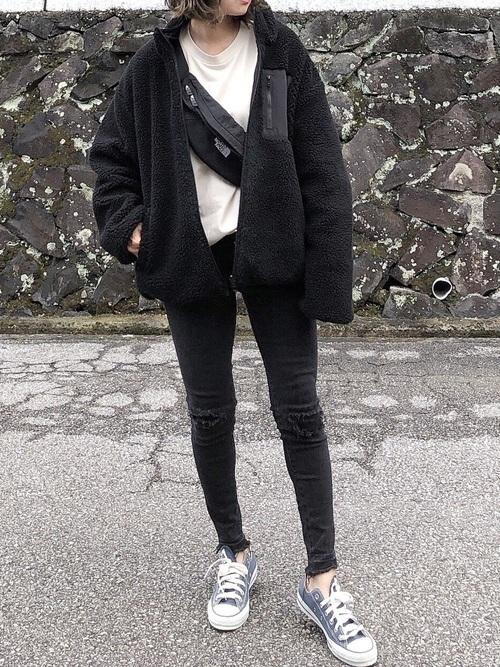 白のトップスに黒のウエストバッグを掛け、黒のボアブルゾンを羽織り、黒のダメージスキニーデニムとグレーのスニーカーを合わせたコーデ