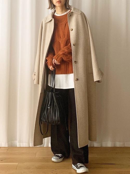 ブラウンのニットに白のTシャツをレイヤードし、ベージュのステンカラーコートを肩掛けし、ダークブラウンのスラックスと黒の巾着ショルダーバッグとブラウンのスニーカーをコーディネート