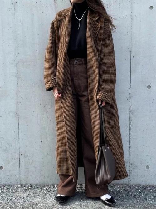 黒のタートルニットにブラウンのチェック柄チェスターコートを羽織り、ブラウンのパンツと黒のバレエシューズ、ショルダーバッグをコーディネート