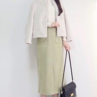 白いジャケット羽織り、白のタートルネックを黄緑色のスカートにインしている女性。