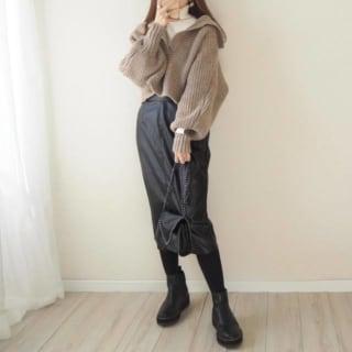白のタートルニットにベージュのクロップド丈ニットを合わせ黒のレザースカートとショートブーツ、チェーンショルダーバッグをコーディネート