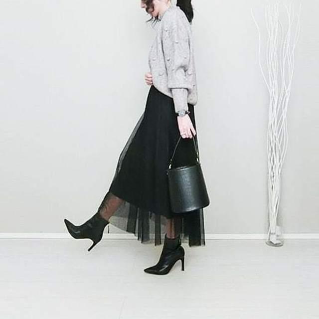 グレーのハイネックニットに黒のチュールスカートを合わせ、黒のショートブーツとバケツバッグをコーディネート