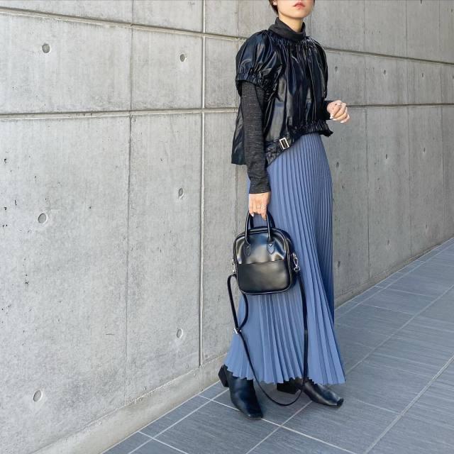 黒のタートルネックプルオーバーに半袖のブラウスを合わせ、くすみブルーのプリーツスカート、スクエアブーツ、ハンドバッグをコーディネート
