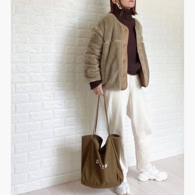 ブラウンのタートルニットに白のデニムを合わせ、ベージュのボアブルゾンを羽織り、白のスニーカーとブラウンのトートバッグをコーディネート
