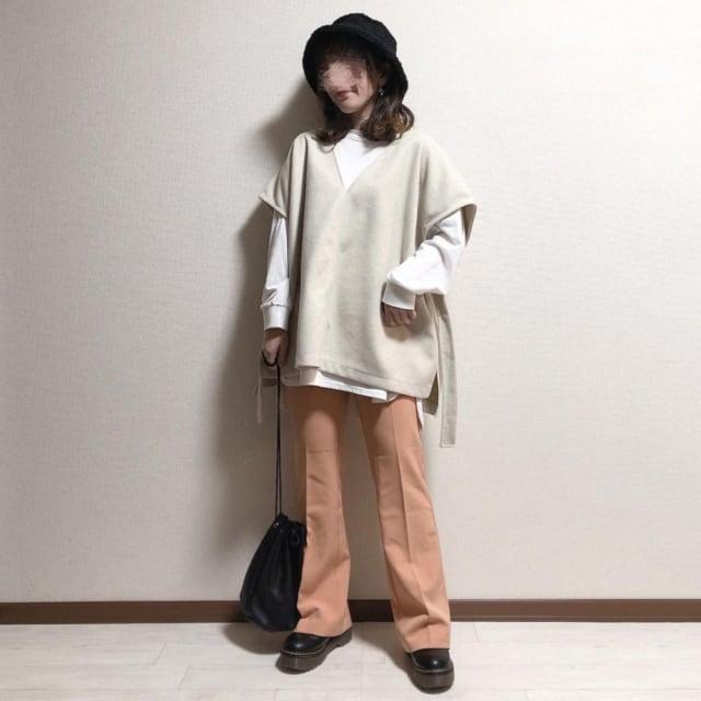 白のインナーにVネックニットベストを合わせベージュのフレアパンツと黒の厚底靴と巾着バッグ、バケハをコーディネート