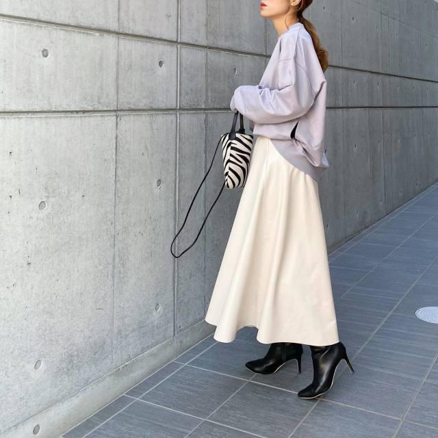 グレーのスウェットに白のフレアスカートを合わせ、黒のヒールブーツ、ゼブラ柄のハンドバッグをコーディネート