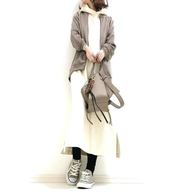 白のパーカーワンピースにグレーのブルゾンを羽織り、グレーのハンドバッグ、ローカットスニーカーをコーディネート