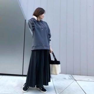 グレーのパーカーに黒のプリーツスカートを合わせ、白のトートバッグ、黒のスニーカーをコーディネート