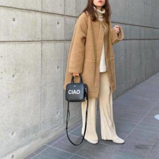 白のタートルネックニットにキャメルカラーのボアコートを羽織り、白のスクエアブーツ、黒のハンドバッグをコーディネート