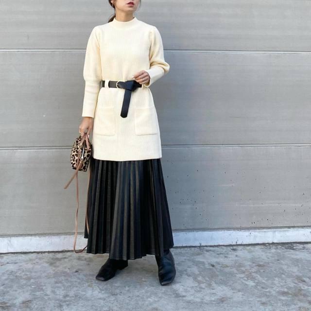 黒ベルト付きモックネック白ニットに黒のレザープリーツスカートを合わせ、スクエアブーツとレオパード柄ショルダーバッグをコーディネート
