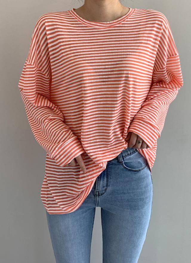 明るめブルーのデニムにオレンジのボーダーTシャツを組み合わせたコーディネート
