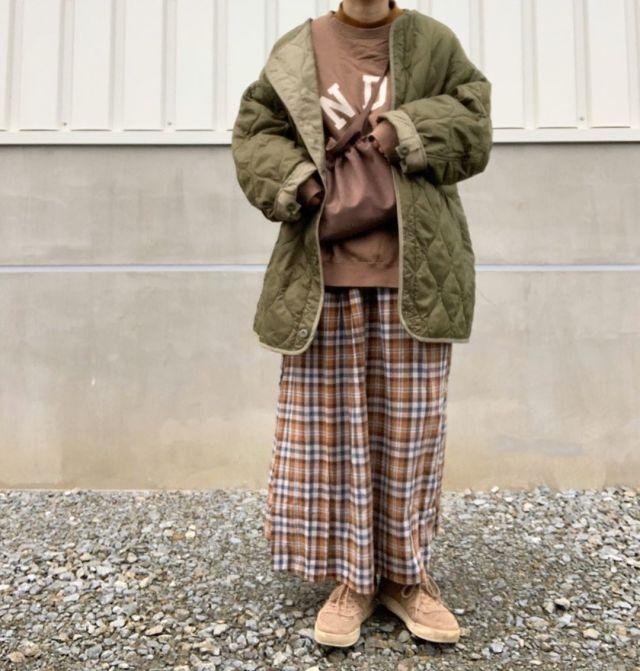 キルティングのコートとチェック柄のスカートを合わせた服装