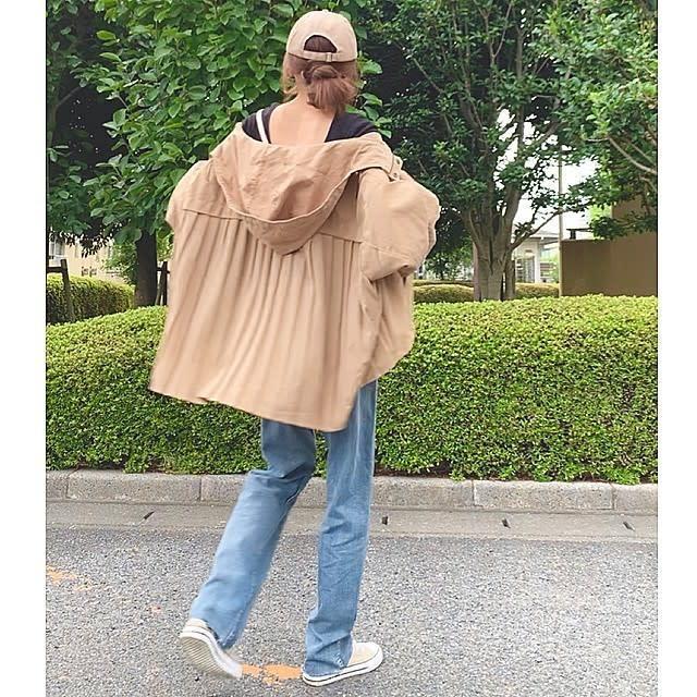 黒Tシャツとジーパンの取り合わせに、ベージュ系の薄手のマウンテンパーカーを羽織ったスタイル