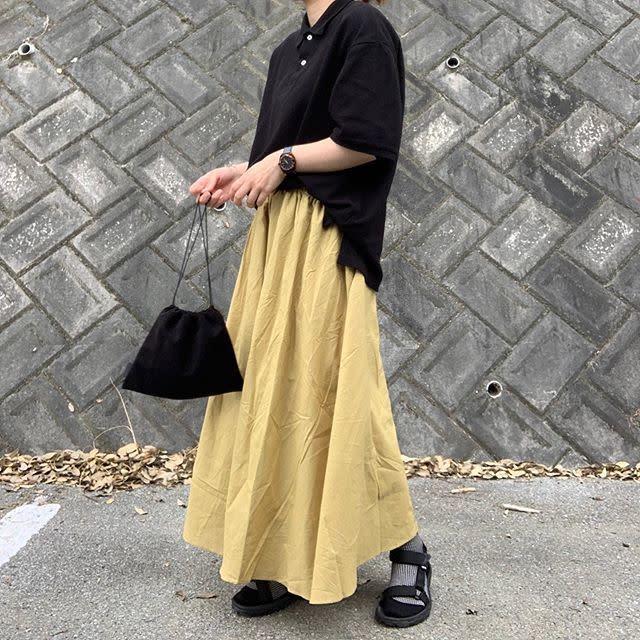 黒のトップスにイエローのスカートのコーデ