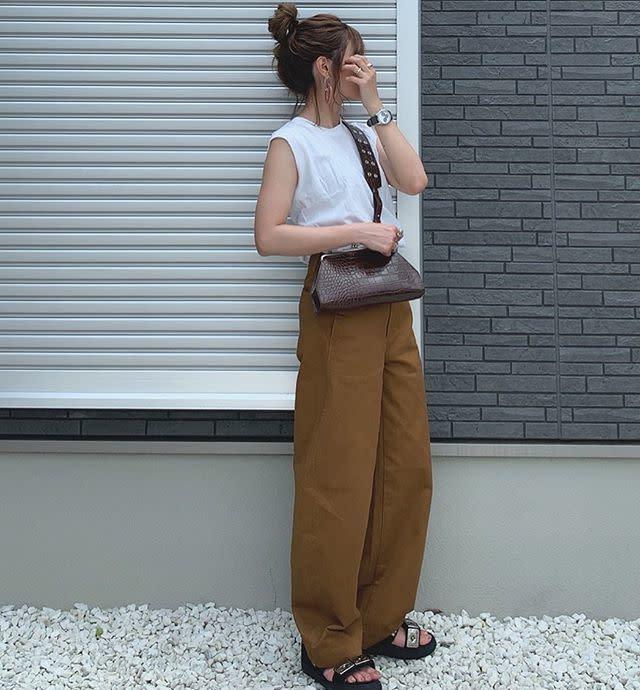 ノースリーブの白Tシャツとブラウンのパンツのコーデ