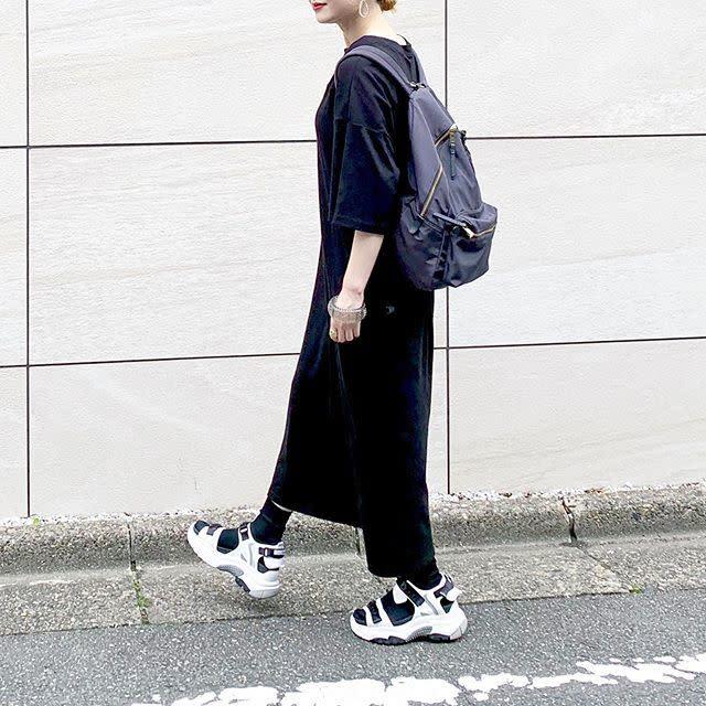 黒のカットソーワンピースとスニーカーを着用した女性