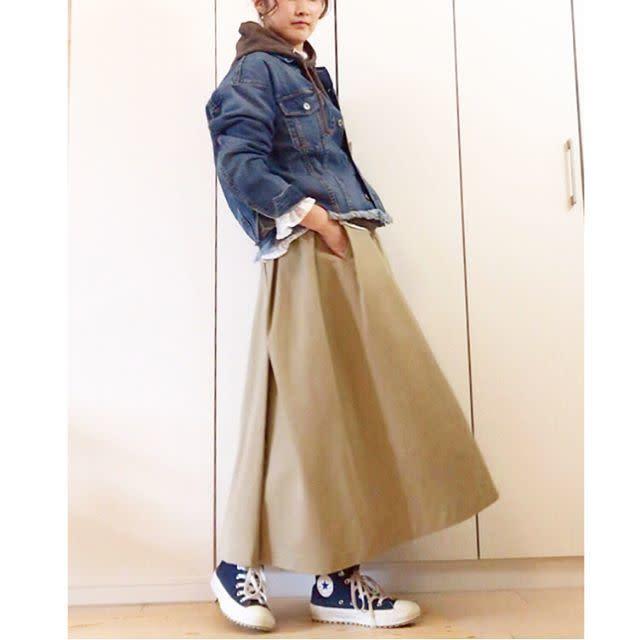 デニムのジャケットとフードとスカートを着用した女性