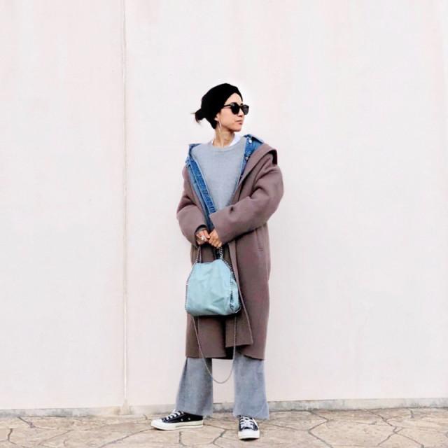 ブラウンのロングコートとデニムジャケットをレイヤードした女性