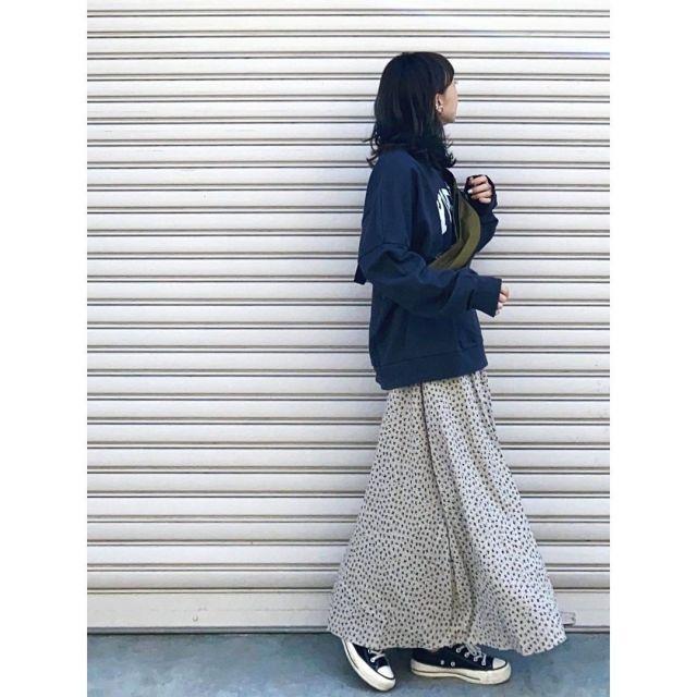 ネイビーのスウェットと花柄スカートを着用した女性