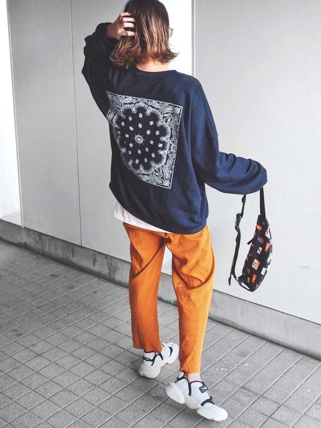 ネイビーのスウェットにオレンジのパンツを着用した女性