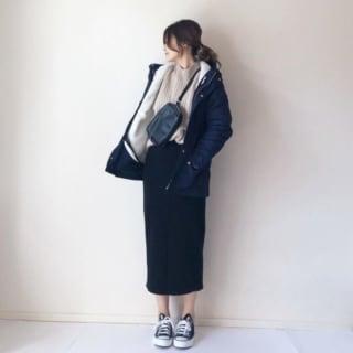 黒のアウターと黒のスカートのコーデにショルダーバッグを斜め掛けにした女性