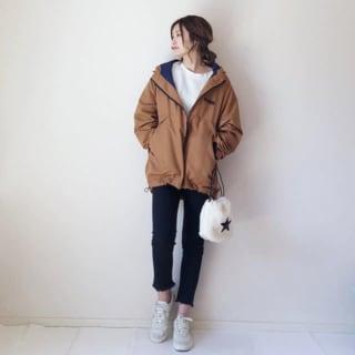 キャメル色のジャケットにパンツスタイルの女性