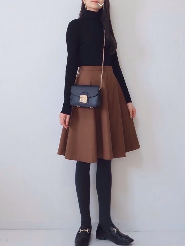 黒のトップスにキャメルのスカート