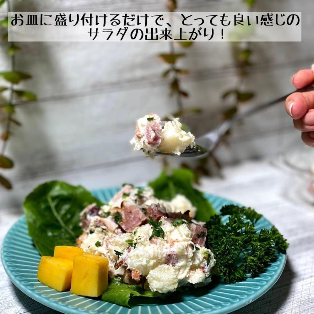 コストコのジャーマンポテトサラダをお皿に盛り付けてスプーンですくっている写真