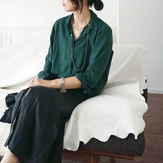モスグリーンのシャツに黒ロングスカートを着た女性