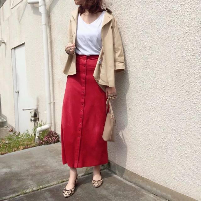 赤のスカートにベージュのジャケットを羽織った女性