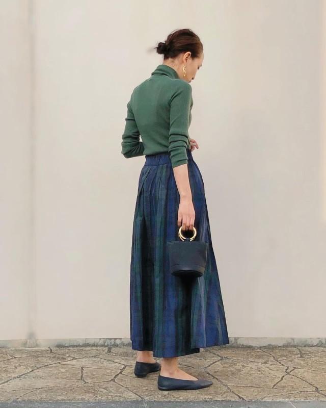 グリーントップスにネイビースカートを合わせたコーデ
