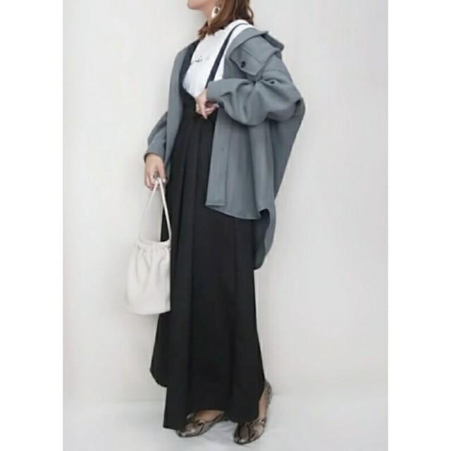 オーバーサイズなカーキのCPOジャケットとスカートのサロペットを着た女性
