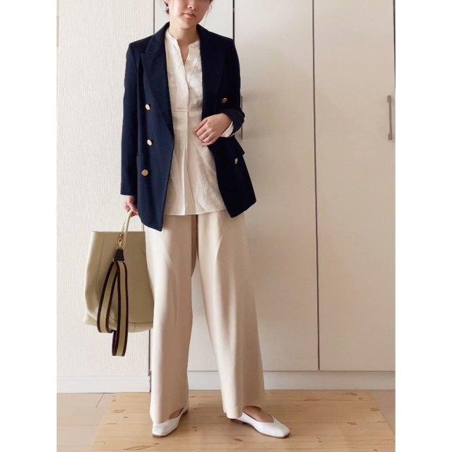 濃紺のテーラードジャケットとベージュのパンツのセットアップ