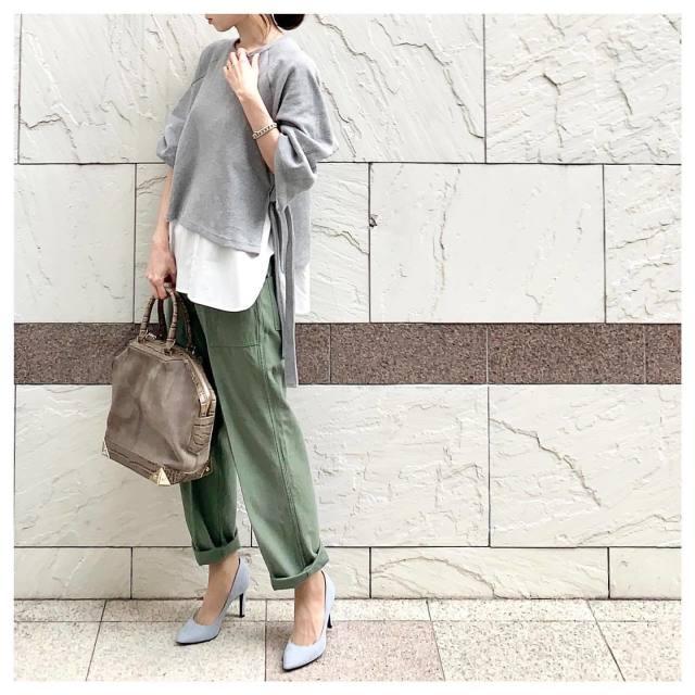 薄いグレーのニットとカーキのカーゴパンツを着た女性
