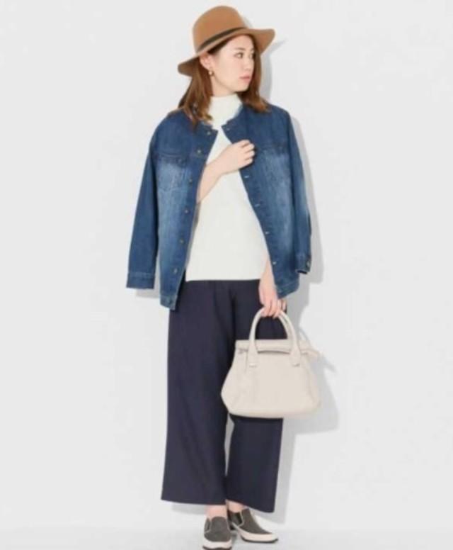 Gジャンを着て白いバッグを持っている女性