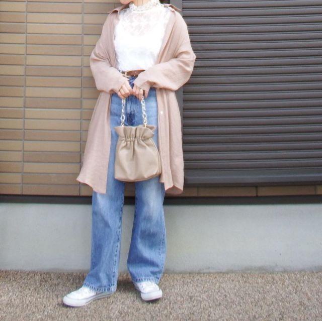 ベージュのロングカーディガンにブルージーンズを着た女性