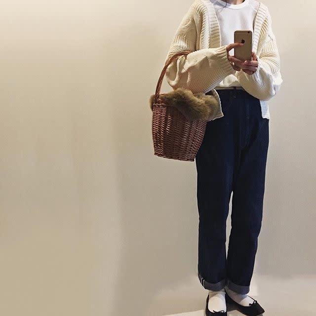ファー付きカゴバックとデニムを着用した女性